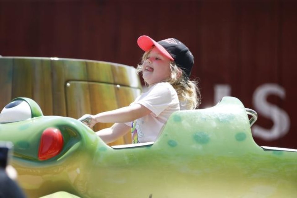 Photo -  Lucy, 5, rides Billy's Frog Hopper in the newly revamped Timber Town kids area of Frontier City on June 28 in Oklahoma City. [Paxson Haws/The Oklahoman]