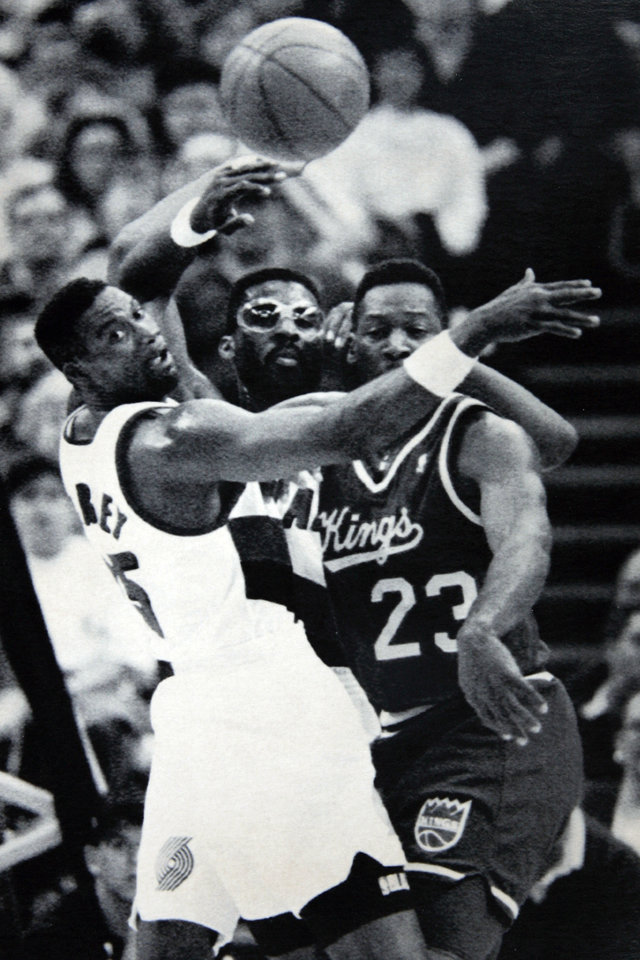 Photo - Former OU basketball player Wayman Tisdale. PORTLAND, ORE., Mar. 7--SURROUNDED-- Sacramento Kings forward Wayman Tisdale (23) flips the ball out against the double-teaming defense of Portland Trail Blazers forwards Jerome Kersey, left, and Buck Williams, center, during NBA action in Portland Friday night. Portland best Sacramento 114-106. (AP Photo) 1992. Photo taken 3/7/1992, photo published unknowen. ORG XMIT: KOD