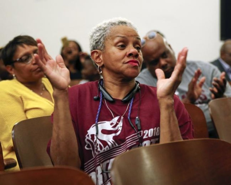 Photo -  Phyllis Crigler applauds Monday after school board member Charles Henry asked about keeping part of the Northeast Academy name with Classen School of Advanced Studies after the two schools merge next school year, during a meeting of the Oklahoma City School Board at Northeast. Crigler graduated from Northeast in 1974. [Nate Billings photos/The Oklahoman]