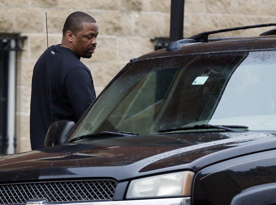 Photo -  Lamont Evans, suspended Oklahoma State assistant head men's basketball coach, gets into a car after leaving the federal courthouse in Oklahoma City on Wednesday. Evans is one of four college coaches charged in a federal investigation focused on fraud and corruption in college basketball. [Photo by Nate Billings, The Oklahoman]