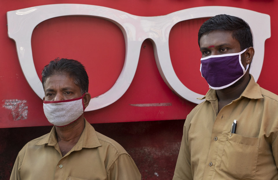 Photo -  Auto rickshaw drivers wearing masks as a precaution against COVID-19 await customers near an optical shop in Kochi, Kerala state, India, Wednesday, June 24, 2020. India is the fourth hardest-hit country by the coronavirus in the world after the U.S., Russia and Brazil. (AP Photo/R S Iyer)