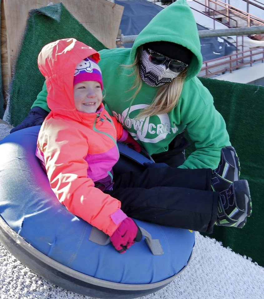 Photo - Snow Crew member Ashlyn Grassman helps Finlea Wallace at the Lifeshare Winterfest & Snow Tubing at the Chickasaw Bricktown Ballpark on Monday, Jan. 1, 2018 in Oklahoma City, Okla. Snow tubing was benched last year as the ballpark was undergoing renovations but returns for the 2019 holiday season. [The Oklahoman Archives]