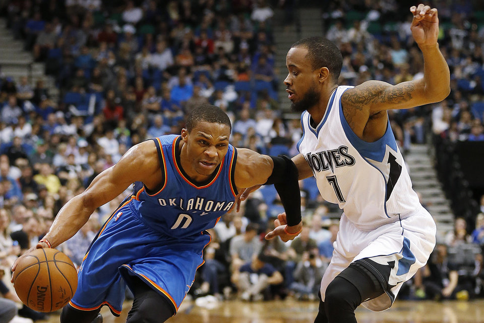 Photo - Oklahoma City Thunder guard Russell Westbrook (0) pushes the ball past Minnesota Timberwolves guard Lorenzo Brown (7) during the second half of an NBA basketball game, Wednesday April 15, 2015, in Minneapolis. The Thunder won 138-113. (AP Photo/Stacy Bengs)