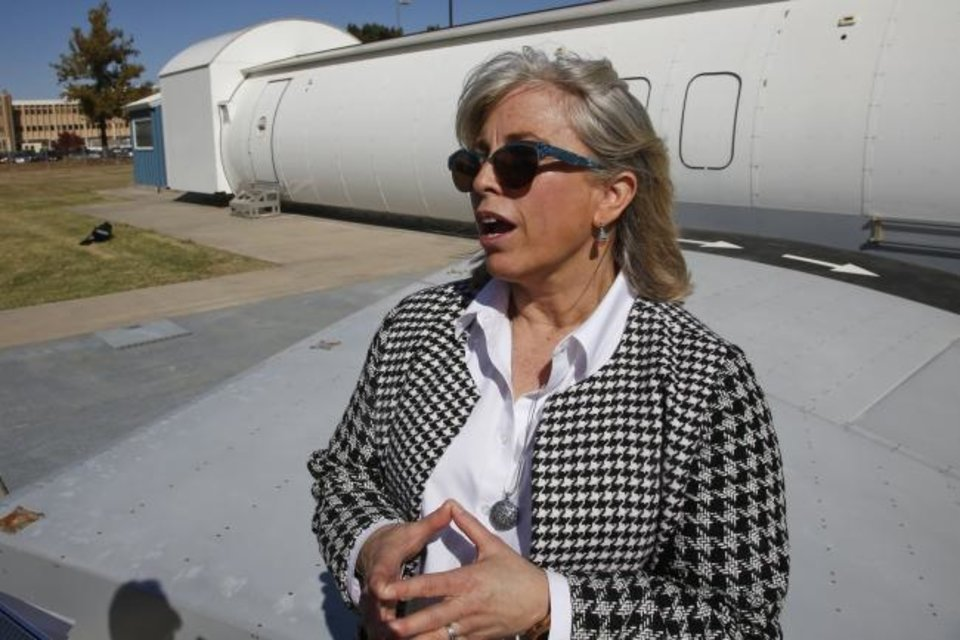 Photo -  Stacey L. Zinke-McKee, a medical-research official at the Federal Aviation Administration facility in Oklahoma City, answers a question in front of an aircraft simulator on Thursday. [AP PHOTO]