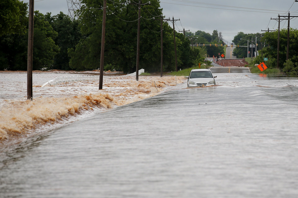 Photo - A vehicle is stranded in floodwaters on NW 206 just west of Portland in Oklahoma City, Tuesday, May 21, 2019. [Bryan Terry/The Oklahoman]