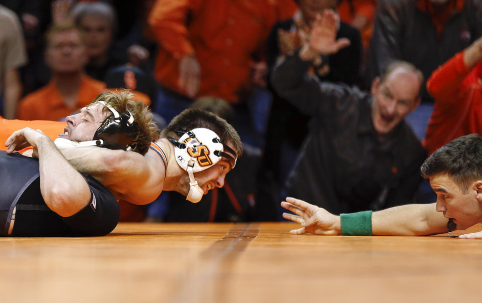 Photo - OSU's Chandler Rogers works on a pin of Iowa's Mitch Bowman during a 174-pound match during a college wrestling dual between the Oklahoma State Cowboys and the Iowa Hawkeyes at Gallagher-Iba Arena in Stillwater, Okla., Sunday, Feb. 24, 2019. OSU won 27-12. Photo by Nate Billings, The Oklahoman