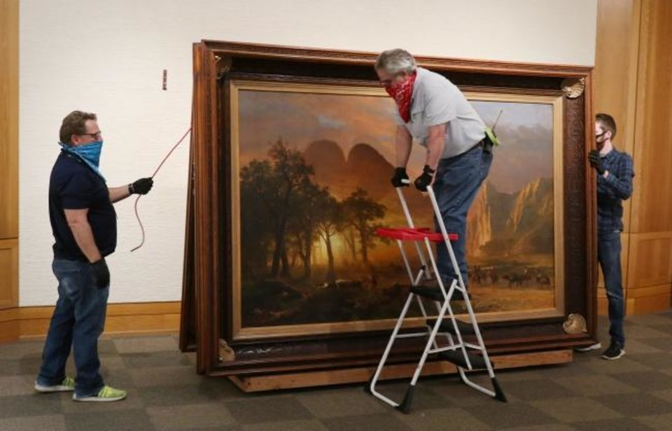 Photo - National Cowboy and Western Heritage Museum is remodeling its Atheron Gallery this summer, revamping the outdated fabric-covered walls and chunky oak buttresses. Staffers were in the midst of the first step of the renovations - removing artwork from the gallery - on June 23. [Doug Hoke/The Oklahoman]