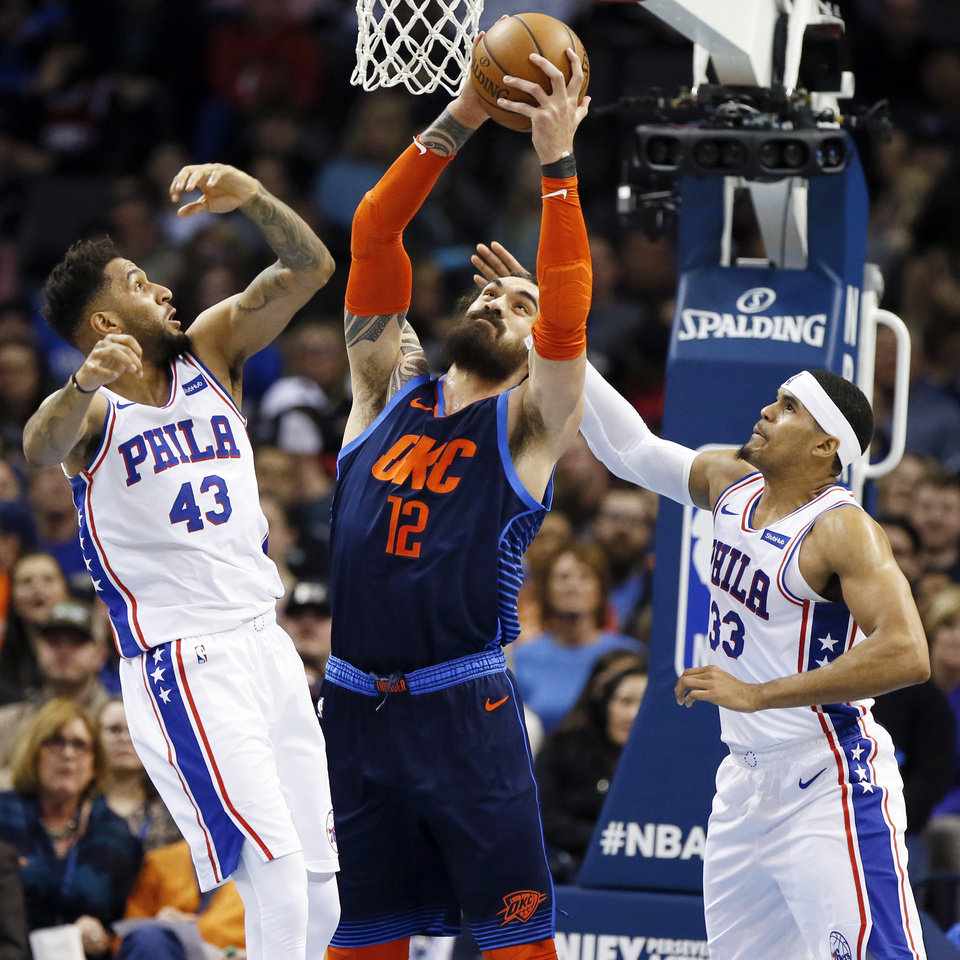 Photo - Oklahoma City's Steven Adams (12) grabs a rebound between Philadelphia's Jonah Bolden (43) and Tobias Harris (33) in the third quarter during an NBA basketball game between the Philadelphia 76ers and the Oklahoma City Thunder at Chesapeake Energy Arena in Oklahoma City, Thursday, Feb. 28, 2019. Philadelphia won 108-104. Photo by Nate Billings, The Oklahoman