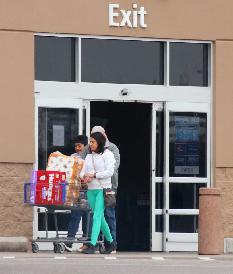 Photo - Shoppers leave the Sam's on north May Ave. with paper goods  Monday, March 16, 2020.  [Photo by Doug Hoke/The Oklahoman]