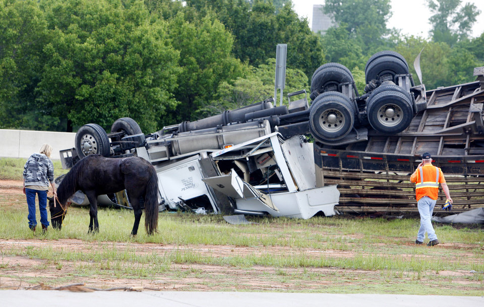 Photo - TRACTOR-TRAILER / SEMI TRUCK / INTERSTATE 35 ENTRANCE / HORSE TRAILER ACCIDENT / OVERTURN / HORSE DEATHS: A semi hauling a stock trailer loaded with horses overturned westbound on the Turner Turnpike at the I-35 exit in Oklahoma City early Tuesday morning, May 18, 2010. The driver fell asleep. Photo by Paul B. Southerland, The Oklahoman ORG XMIT: KOD