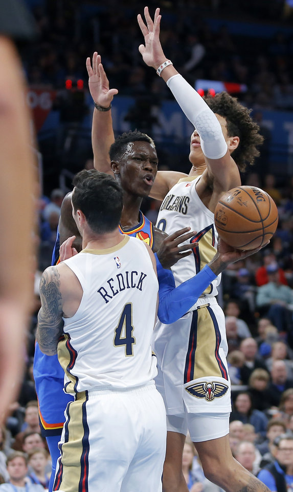 Photo - Oklahoma City's Dennis Schroder (17) passes the ball from between New Orleans' JJ Redick (4) and Jaxson Hayes (10) during an NBA basketball game between the Oklahoma City Thunder and the New Orleans Pelicans at Chesapeake Energy Arena in Oklahoma City, Saturday, Nov. 2, 2019. Oklahoma City won 115-104. [Bryan Terry/The Oklahoman]