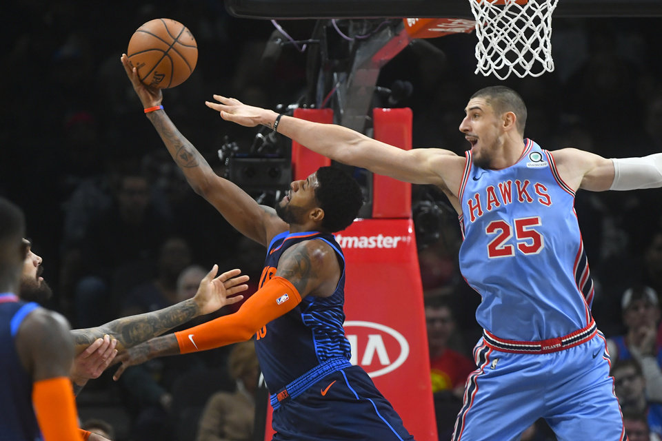 Photo -  Oklahoma City Thunder forward Paul George attempts a reverse layup as Atlanta Hawks center Alex Len defends during Tuesday's game in Atlanta. [AP Photo]