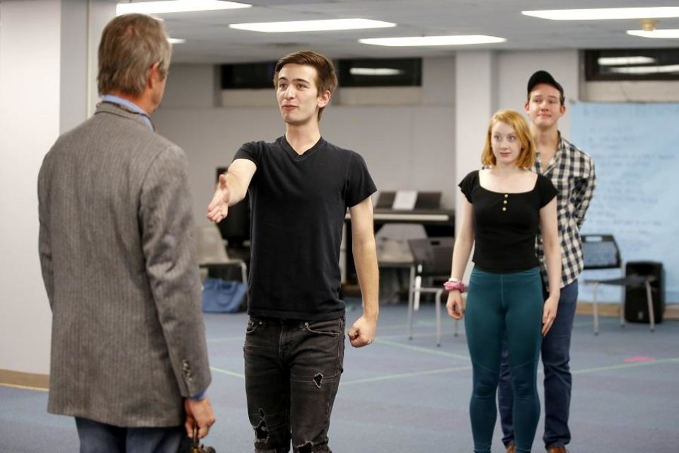 Photo - Trevor Rau, as Dill, reaches out to shake the hand of Eric Starkey, as Atticus, while Megan Berning, as Scout, and Andrew Lewis, as Jem, look on during a rehearsal for Oklahoma Children's Theatre and TheatreOCU's co-production of