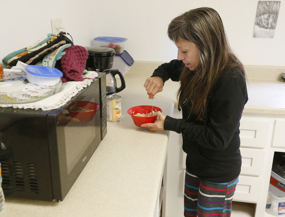 Photo -  Leslie Watson, a client at Ray's House, prepares oats in the women's area at the facility in Muskogee. [Photo by Nate Billings, The Oklahoman]