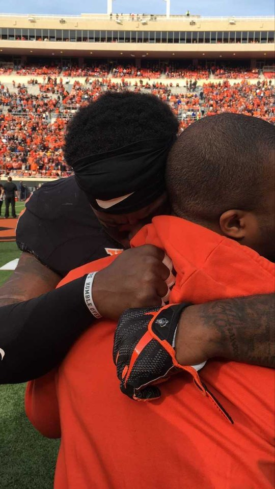 Photo -  Oklahoma State's Enoch Smith Jr. cries while hugging his younger brother, Trey, during OSU's senior day ceremony in November. [Photo provided]
