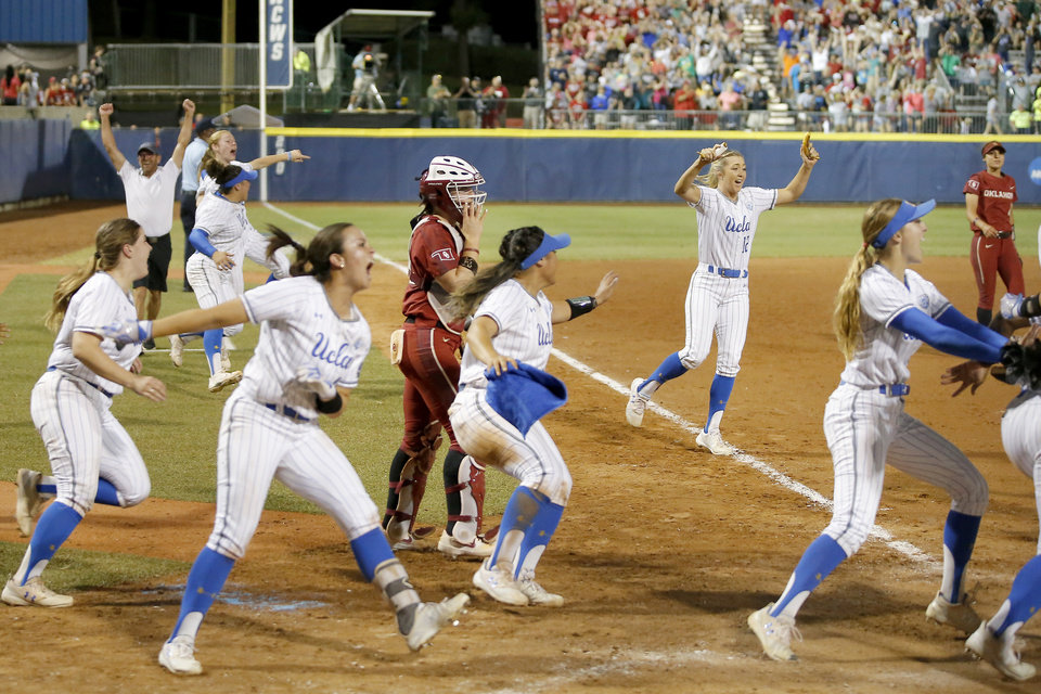 Photo - UCLA celebrates as Oklahoma's Lynnsie Elam (22) walks off the field in the second NCAA softball game in the championship series of the Women's College World Series between Oklahoma and UCLA at USA Softball Hall of Fame Stadium in Oklahoma City, Tuesday, June 4, 2019. UCLA won 5-4. [Bryan Terry/The Oklahoman]