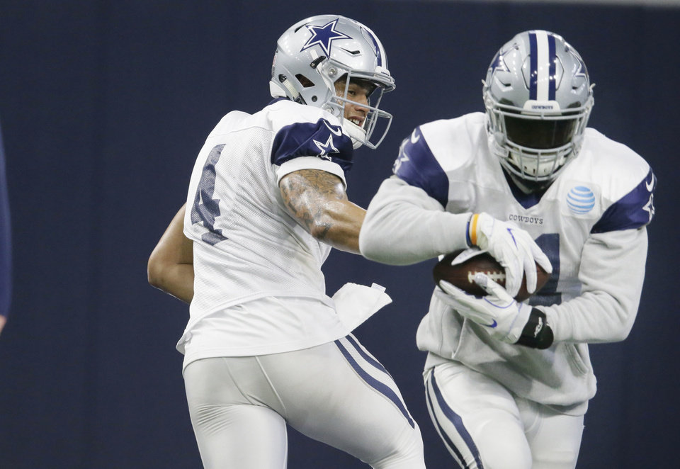 Photo - Cowboy quarterback Dak Prescott hands off to tailback Ezekiel Elliott during a Dallas practice this week. The rookies have led the Cowboys into the NFC semifinals against Green Bay on Sunday. (AP Photo)