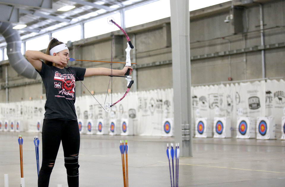 Photo -  LOWER RIGHT: Mustang eighth-grader Adisen Williamson competes Wednesday in the archery competition.  [photos by Sarah Phipps/The Oklahoman]