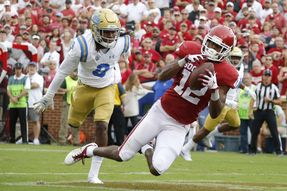 Photo - Oklahoma's A.D. Miller (12) catches a touchdown pass in front of UCLA's Elijah Gates (9) during a college football game between the University of Oklahoma Sooners (OU) and the UCLA Bruins at Gaylord Family-Oklahoma Memorial Stadium in Norman, Okla., Saturday, Sept. 8, 2018. Oklahoma won 49-21. Photo by Bryan Terry, The Oklahoman