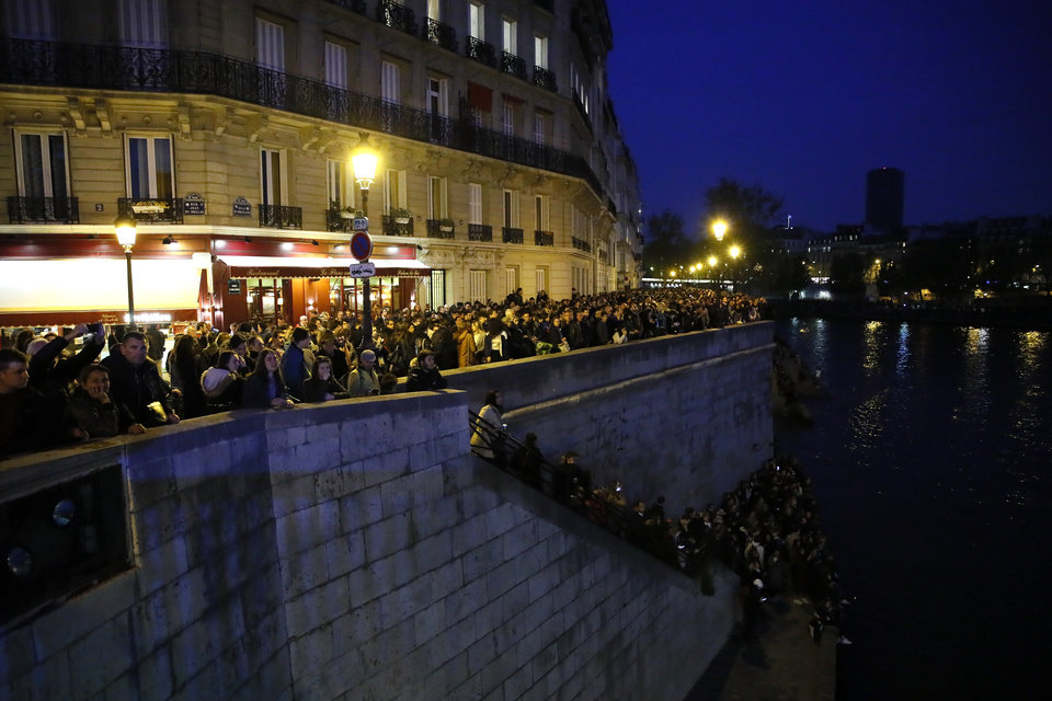 Photo - People watch Notre Dame cathedral burning from the Seine river banks in Paris, Monday, April 15, 2019. A catastrophic fire engulfed the upper reaches of Paris' soaring Notre Dame Cathedral as it was undergoing renovations Monday, threatening one of the greatest architectural treasures of the Western world as tourists and Parisians looked on aghast from the streets below. (AP Photo/Francois Mori)