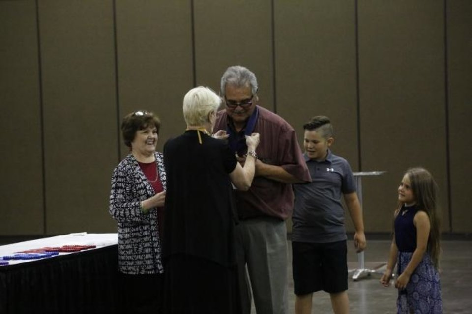 Photo -  Clancy Gray receives his medal for his third place finish in the oil and acrylic painting category from past Red Earth Board President Teri Stanek at the 2019 Red Earth Festival at the Cox Convention Center in Oklahoma City, Oklahoma Friday, June 7, 2019. Gray also placed second in sculpture. [Paxson Haws/The Oklahoman]