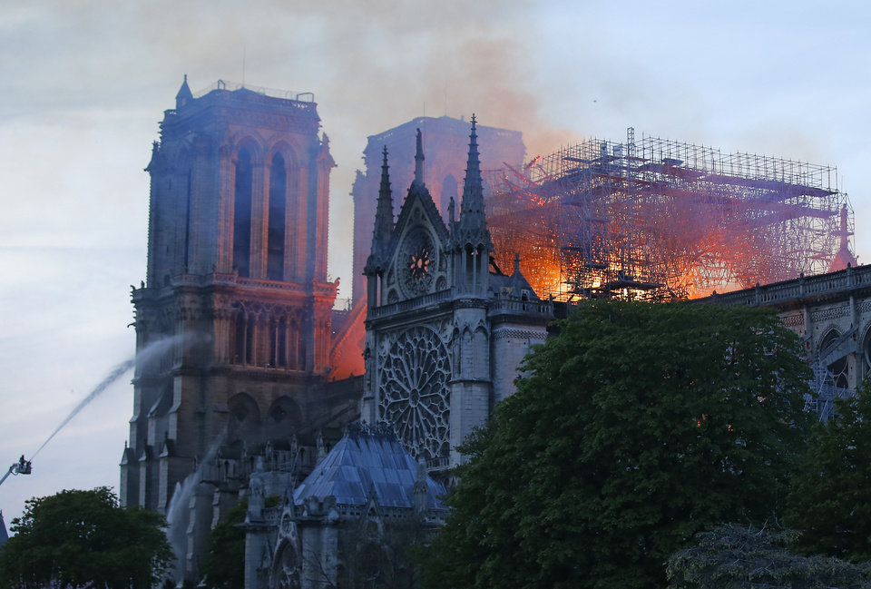 Photo - A firefighter tackles the blaze as flames and smoke rise from Notre Dame cathedral as it burns in Paris, Monday, April 15, 2019. Massive plumes of yellow brown smoke is filling the air above Notre Dame Cathedral and ash is falling on tourists and others around the island that marks the center of Paris. (AP Photo/Michel Euler)