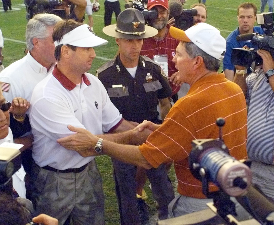 Photo - COLLEGE FOOTBALL: OU head coach Bob Stoops shakes hands with Texas coach Mack Brown after beating Texas in the Red River Shootout. University of Oklahoma against University of Texas, Sat., Oct 12, 2002 at the Cotton Bowl in Texas. Staff photo by Paul Hellstern