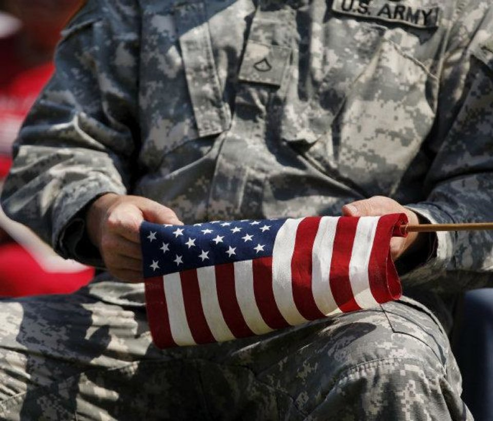 Photo - A soldier holds an American flag in his lap during the 2010 Memorial Day observance at the 45th Infantry Division Museum, 2145 NE 36. Oklahoman Archive photo by Jim Beckel  JIM BECKEL