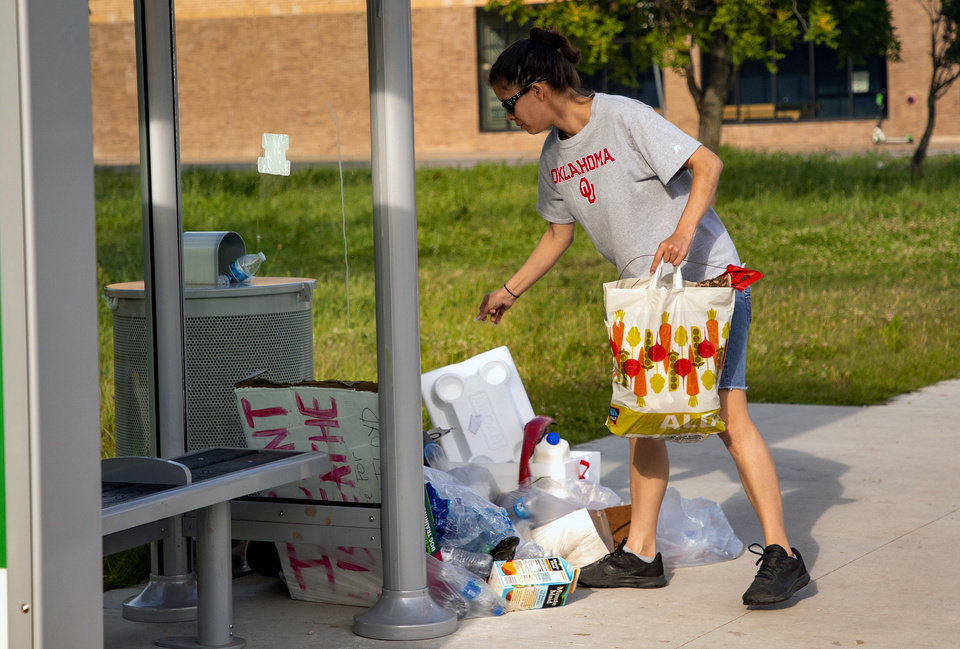 Photo - Erica Baysinger volunteers to clean up trash near NW 4th and Shartel Ave. on Monday, June 1, 2020, in Oklahoma City, Okla. that was left behind from the George Floyd protest on Sunday.   [Chris Landsberger/The Oklahoman]
