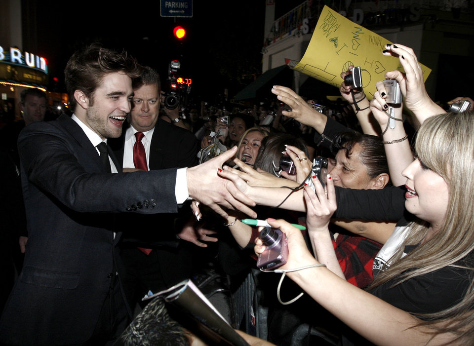 Photo - Actor Robert Pattinson signs autographs as he arrives at The Twilight Saga: New Moon premiere in Westwood, Calif. Monday, Nov. 16, 2009.  (AP Photo/Matt Sayles) ORG XMIT: CAGS137