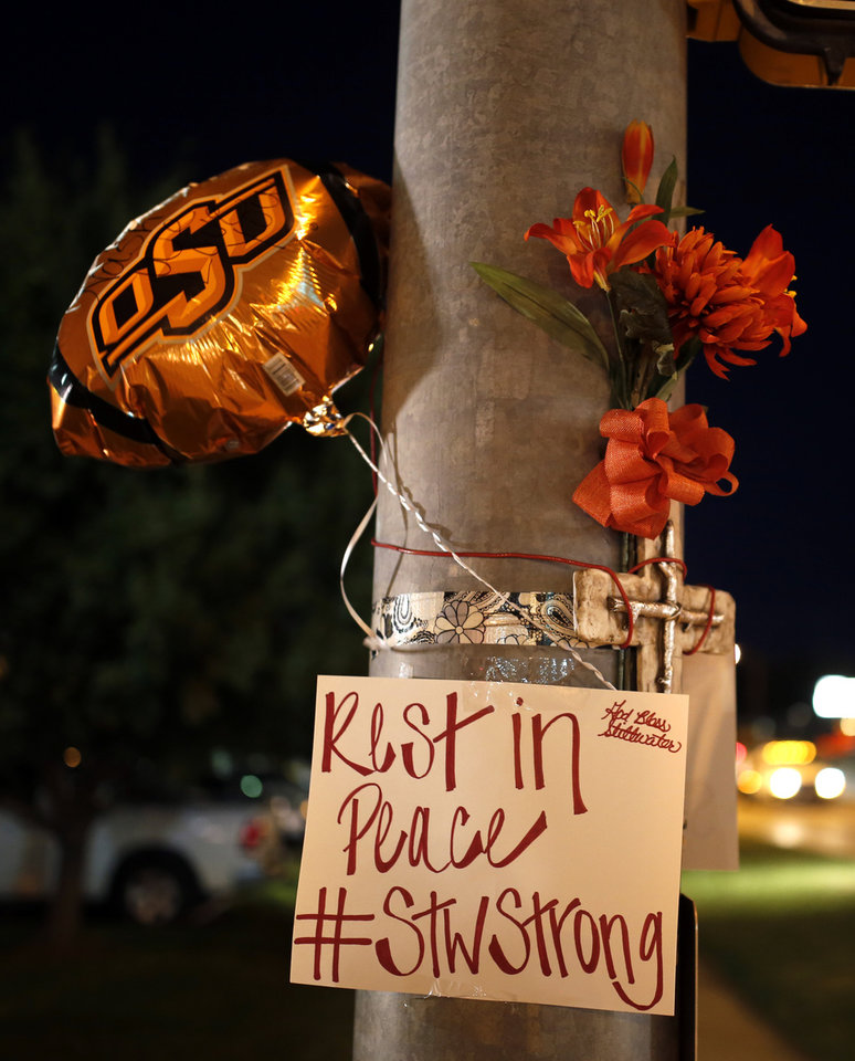 Photo - A memorial is pictured at Main and Hall of Fame where earlier a car crashed into spectators during the Oklahoma State University homecoming parade killing 4 people and injured several in Stillwater, Okla., Saturday, Oct. 24, 2015. Photo by Sarah Phipps, The Oklahoman