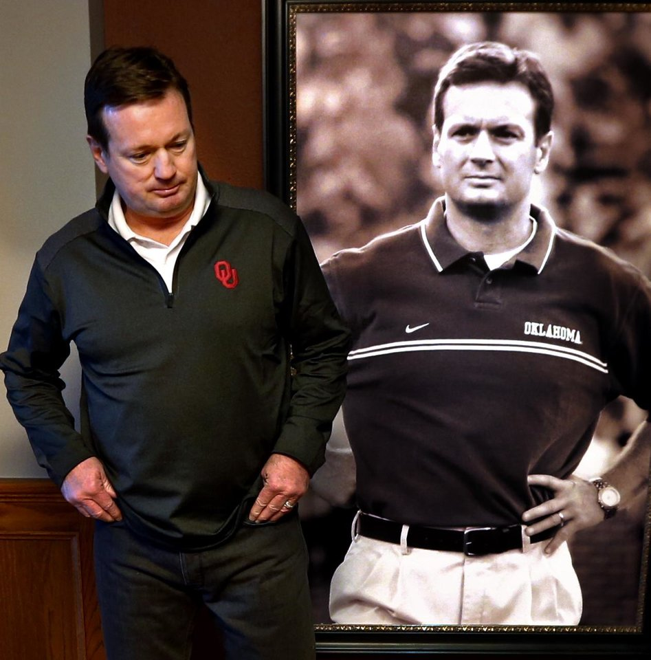 Photo - University of Oklahoma (OU) head football coach Bob Stoops stands in front of an early portrait as he speaks with Oklahoman reporter Berry Tramel on Tuesday, Jan. 6, 2015 in Norman, Okla.  Photo by Steve Sisney, The Oklahoman
