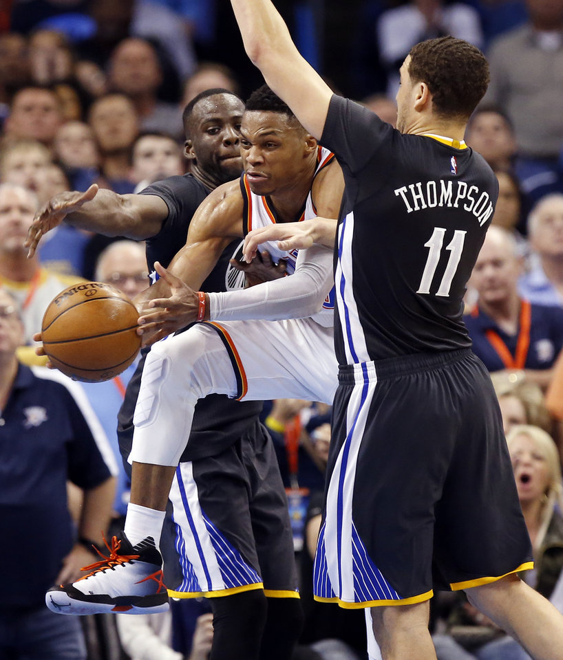 Photo - Oklahoma City's Russell Westbrook (0) passes between Golden State's Draymond Green (23) and Klay Thompson (11) in overtime during an NBA basketball game between the Oklahoma City Thunder and the Golden State Warriors at Chesapeake Energy Arena in Oklahoma City, Saturday, Feb. 27, 2016. Golden State won 121-118 in overtime. Photo by Nate Billings, The Oklahoman
