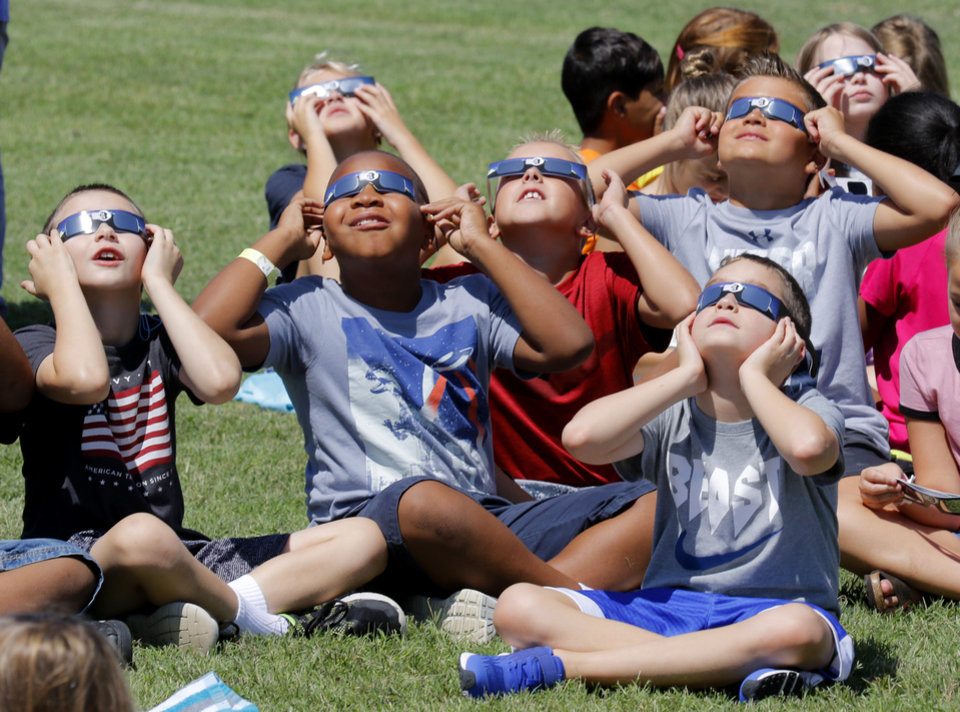 Photo -  Students at Washington Irving Elementary School watch the eclipse Monday in Edmond. [Photo By Steve Gooch, The Oklahoman]