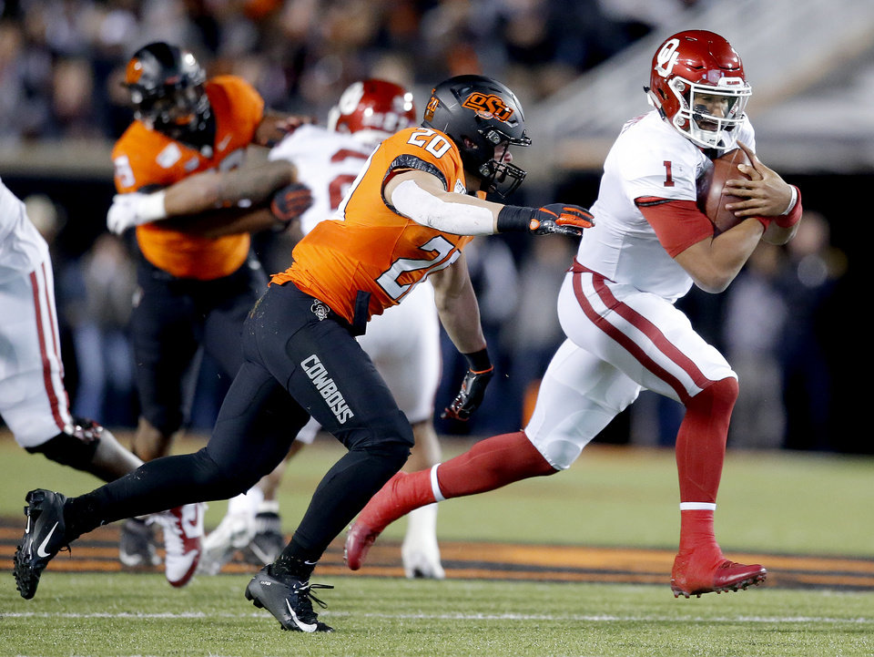 Photo - Oklahoma's Jalen Hurts (1) rushes as he his chase by Oklahoma State's Malcolm Rodriguez (20) during the Bedlam college football game between the Oklahoma State Cowboys (OSU) and Oklahoma Sooners (OU) at Boone Pickens Stadium in Stillwater, Okla., Saturday, Nov. 30, 2019. OU won  34-16. [Sarah Phipps/The Oklahoman]