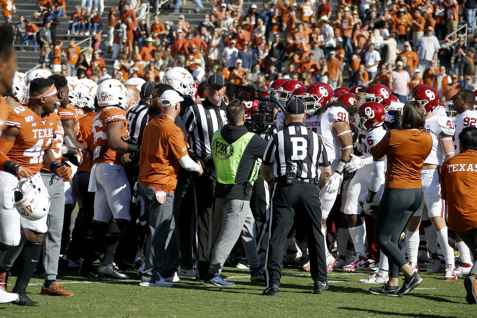 Photo - Oklahoma and Texas players argue before the Red River Showdown college football game between the University of Oklahoma Sooners (OU) and the Texas Longhorns (UT) at Cotton Bowl Stadium in Dallas, Saturday, Oct. 12, 2019. Oklahoma won 34-27. [Bryan Terry/The Oklahoman]