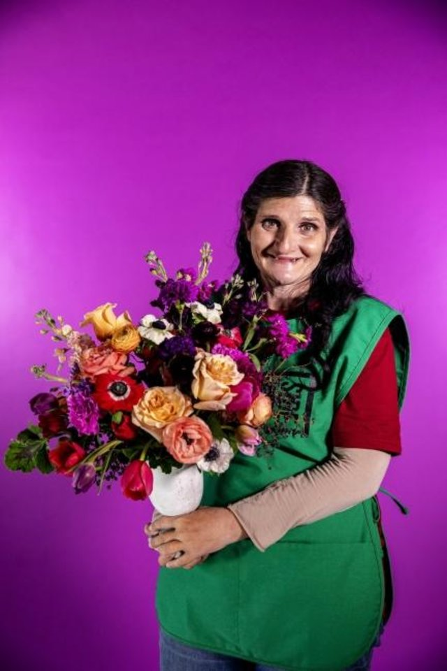 Photo -  Gina holds a bouquet at Curbside Flowers, a new full-service flower shop that is a program of the Homeless Alliance.  Every bouquet is made by a Curbside vendor, providing meaningful employment to someone transitioning out of homelessness. [Photo provided by Nathan Poppe]