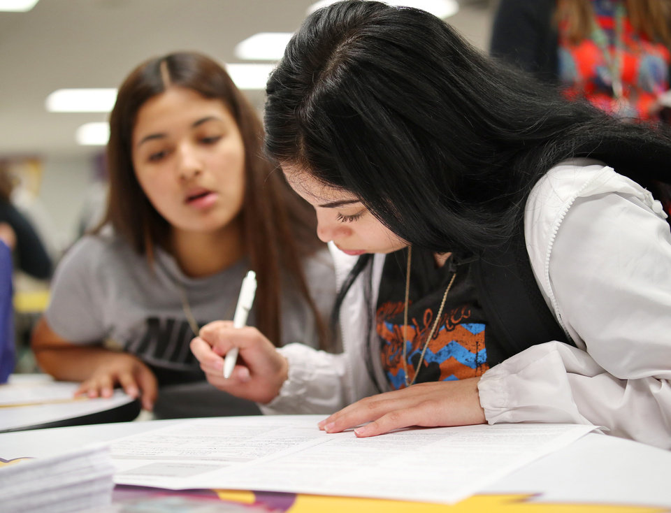 Photo - Magaly Ramirez, 17, looks to Diamond Alvarez, 18, while filling out the registration form. Generation Citizen set up at Northwest Classen High School during lunch to register students age 17 and older to vote, Wednesday, September 25, 2019. [Doug Hoke/The Oklahoman]