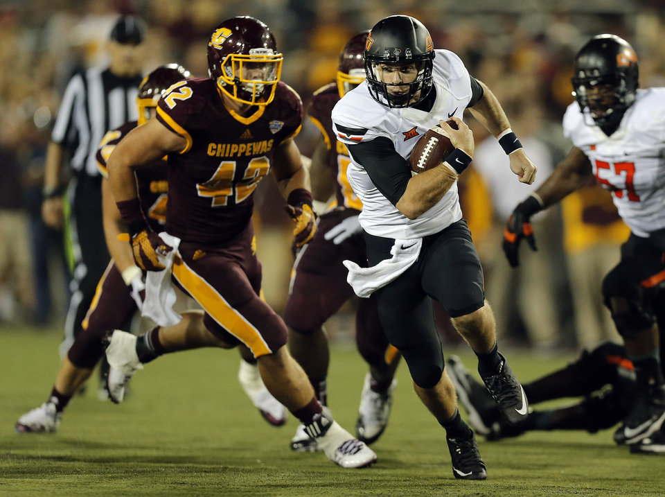 Photo - Oklahoma State's J.W. Walsh (4) rushes as Central Michigan's Nathan Ricketts (42) chases him down during the college football game between the Central Michigan Chippewas and the Oklahoma State University Cowboys at the Kelly-Shorts Stadium in Mount Pleasant, Mich., Thursday, Sept. 3, 2015. Photo by Sarah Phipps, The Oklahoman