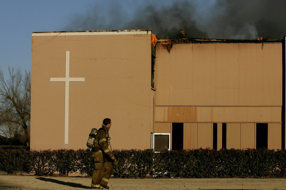 Photo - An Edmond firefighter walks by a fire at an annex building at New Covenant United Methodist Church at 2300 S Boulevard in Edmond. BY BRYAN TERRY, THE OKLAHOMAN ORG XMIT: KOD