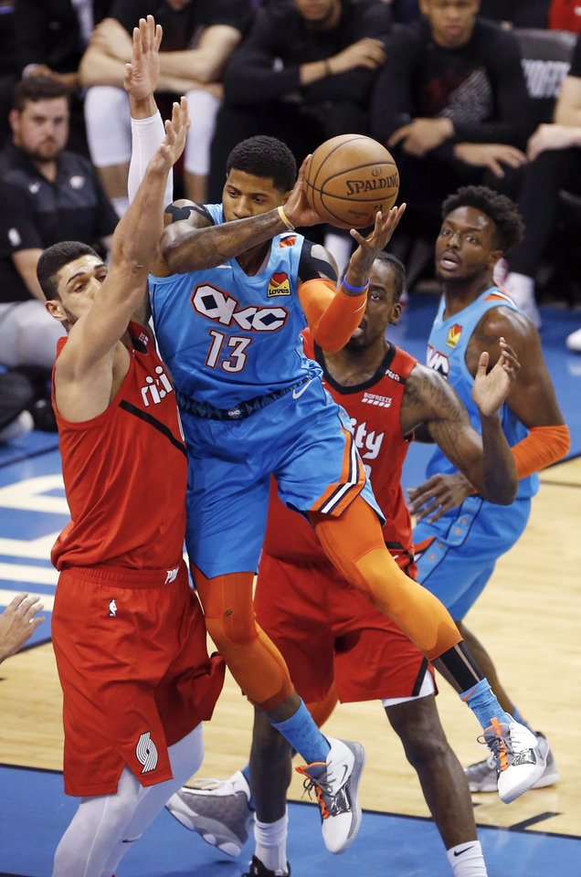 Photo - Oklahoma City's Paul George (13) passes away from Portland's Enes Kanter (00), left, and Maurice Harkless (4) as Oklahoma City's Jerami Grant (9), right, looks on in the first quarter during Game 3 in the first round of the NBA playoffs between the Portland Trail Blazers and the Oklahoma City Thunder at Chesapeake Energy Arena in Oklahoma City, Friday, April 19, 2019. Photo by Nate Billings, The Oklahoman