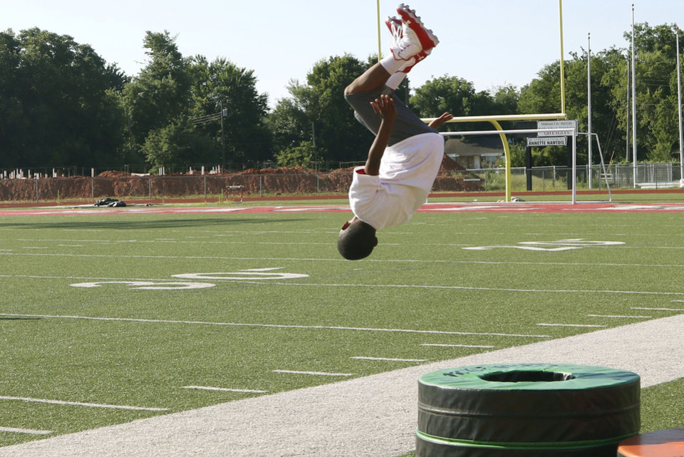 Photo - A camp participant does a back flip off equipment at Los Angeles Chargers player Jeff Richards Elite Football Camp at Del City High School in Del City, Oklahoma on July 13, 2019. [Paxson Haws/The Oklahoman]
