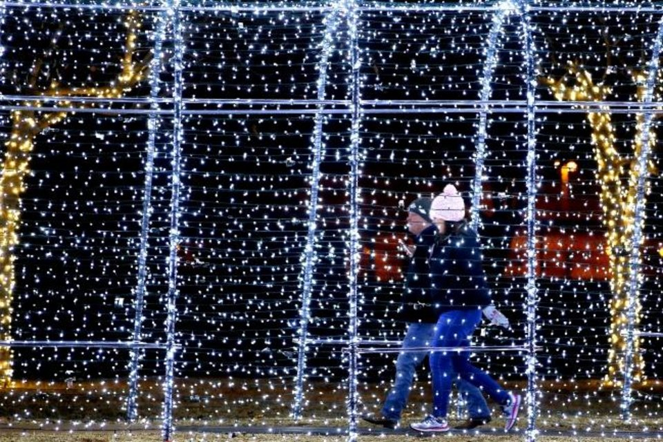 Photo -  Visitors to Edmond's Mitch Park walk through a light display during a previous year's Luminance event. [BRYAN TERRY/THE OKLAHOMAN ARCHIVES]