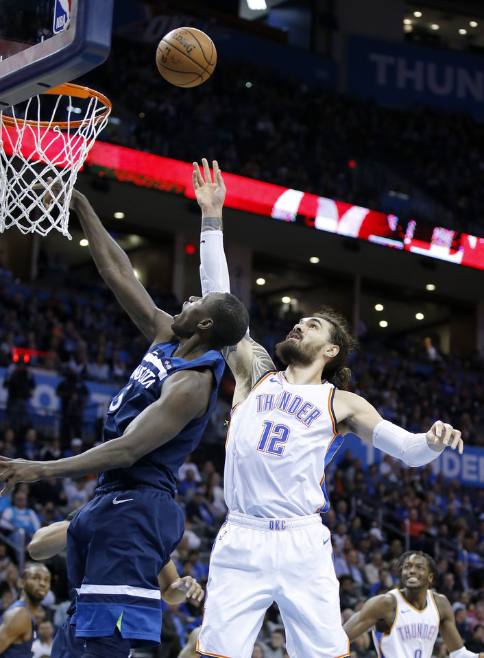 Photo - Oklahoma City's Steven Adams (12) shoots as Minnesota's Gorgui Dieng (5) defends during the NBA game between the Oklahoma City Thunder and Minnesota Timberwolves at the Chesapeake Energy Arena, Tuesday, Jan. 8, 2019. Photo by Sarah Phipps, The Oklahoman