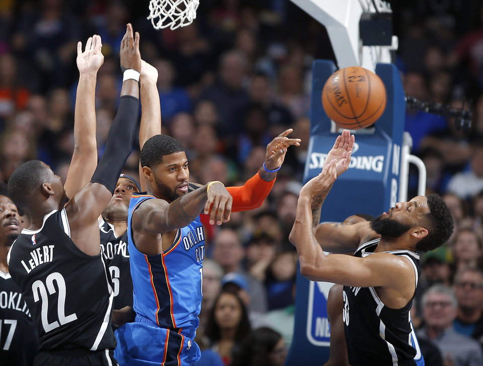 Photo - Oklahoma City's Paul George (13) passes from between Brooklyn's Caris LeVert (22), Jared Dudley (6) and Allen Crabbe (33) during an NBA basketball game between the Oklahoma City Thunder and the Brooklyn Nets at Chesapeake Energy Arena in Oklahoma City, Wednesday, March 13, 2019. Photo by Bryan Terry, The Oklahoman