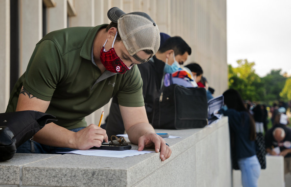 Photo - People, who began camping out 8pm Thursday evening, fill out paperwork as they wait in line outside the Oklahoma Employment Securities Commission (OESC) to try and resolve issues that have prevented them from receiving unemployment payments on Friday, June 26, 2020, in Oklahoma City, Okla.   [Chris Landsberger/The Oklahoman]  .