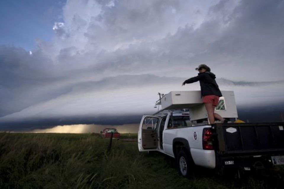 Photo -  Elizabeth Smith, researcher with the University of Oklahoma Cooperative Institute for Mesoscale Meteorological Studies, prepares the lidar system for operation during a storm. [MIKE CONIGLIO/NOAA NSSL]