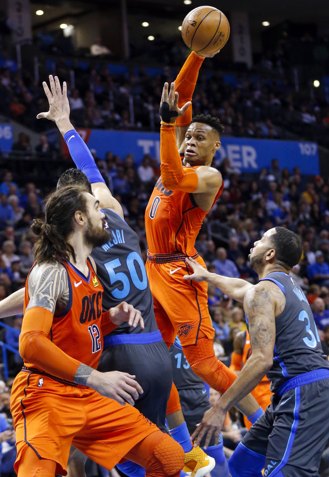 Photo - Oklahoma City's Russell Westbrook (0) passes the ball to Steven Adams (12) over Dallas' Salah Mejri (50) and Devin Harris (34) in the second quarter during an NBA basketball game between the Dallas Mavericks and the Oklahoma City Thunder at Chesapeake Energy Arena in Oklahoma City, Sunday, March 31, 2019. Photo by Nate Billings, The Oklahoman