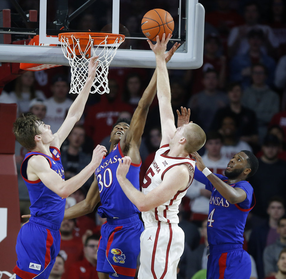 Photo - Oklahoma's Brady Manek (35) goes to the basket between Kansas' Christian Braun (2), left, Ochai Agbaji (30) and Isaiah Moss (4) during an NCAA college basketball game between the University of Oklahoma Sooners (OU) and the University of Kansas Jayhawks at Lloyd Noble Center in Norman, Okla., Tuesday, Jan. 14, 2020. [Bryan Terry/The Oklahoman]