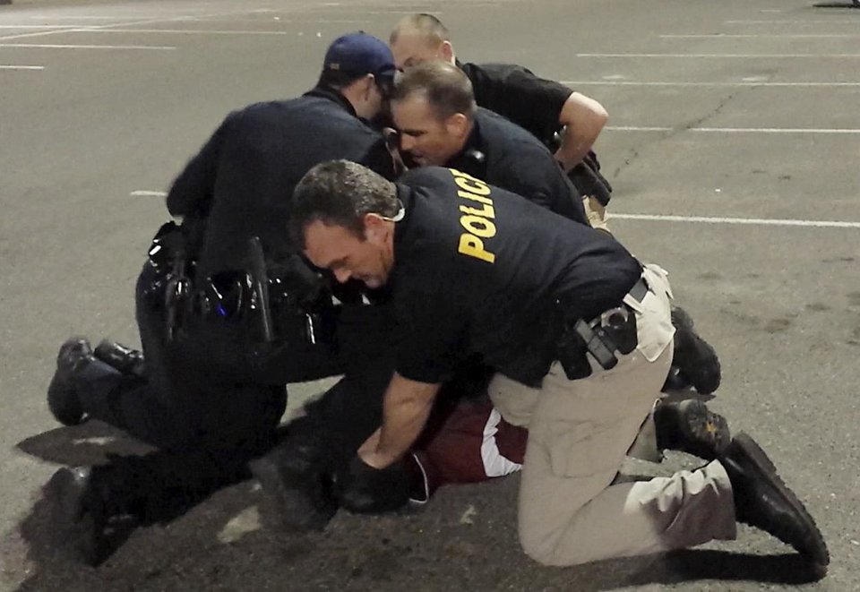 Photo - Moore Police officers restrain Luis Rodriguez in the parking lot at the Warren Theater. Photo provided.